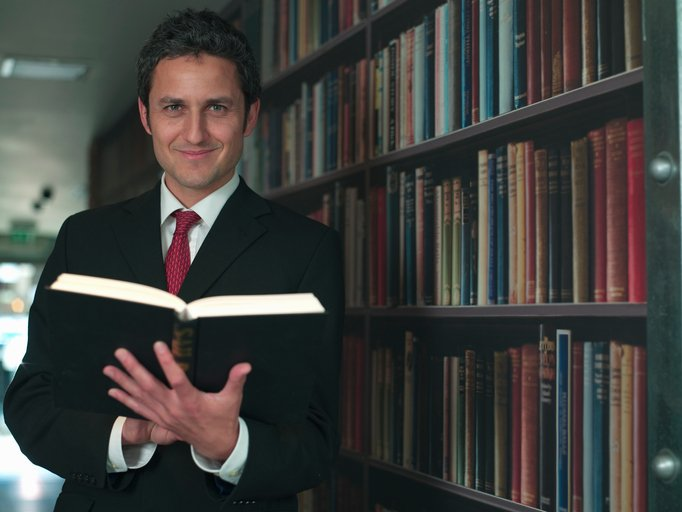 A man standing in front of a bookcase full of books holding an open book