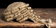 A blonde barrister wig rests on a wooden desk