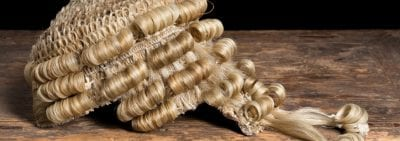 A blonde barrister wig rests on a wooden desk