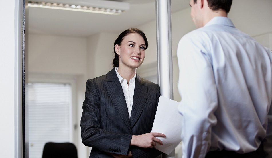 Smartly-dressed woman talking to person in an office asking the best questions on an open day