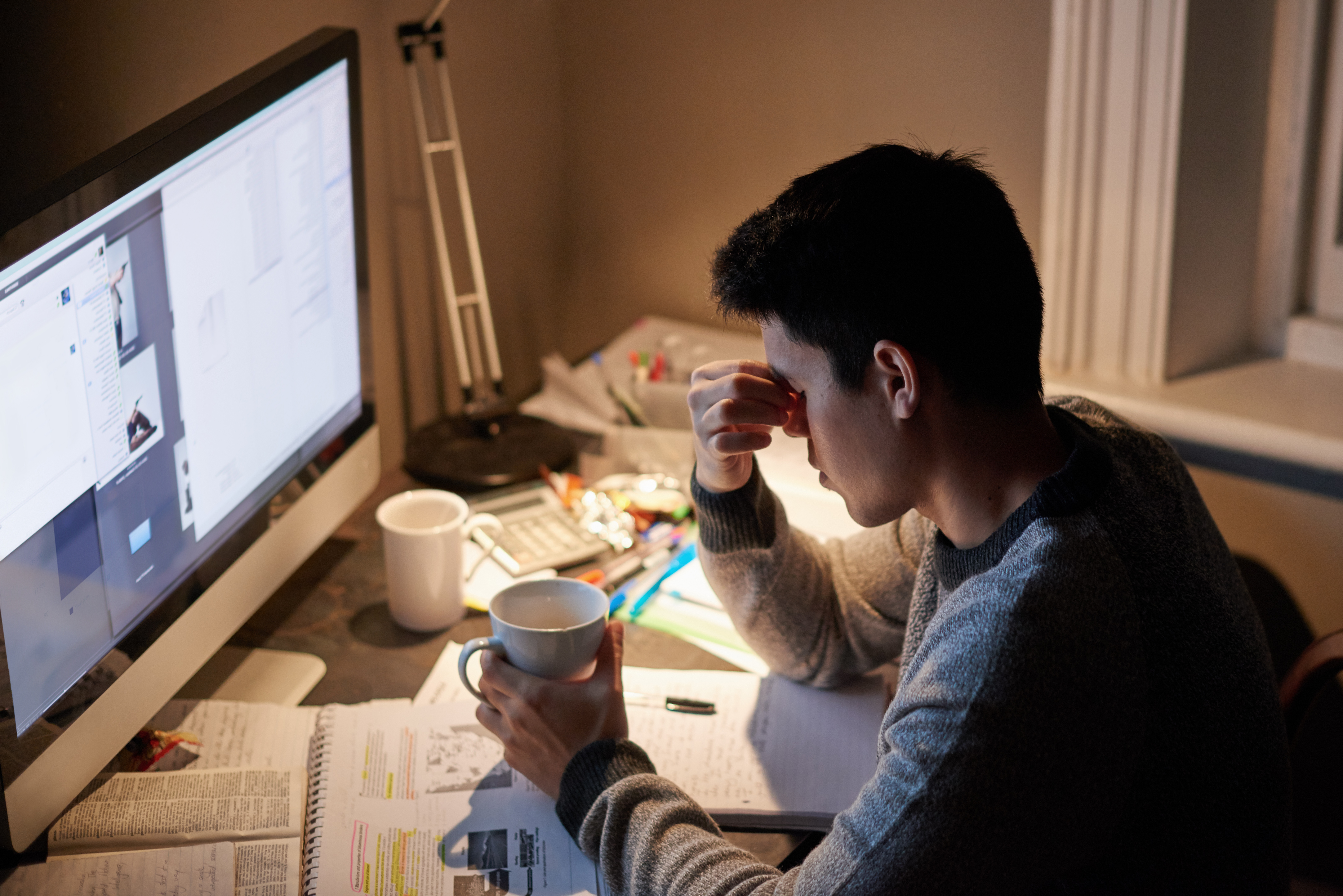 A young man sits at his desk in front of a desktop computer screen looking upset as he holds a mug