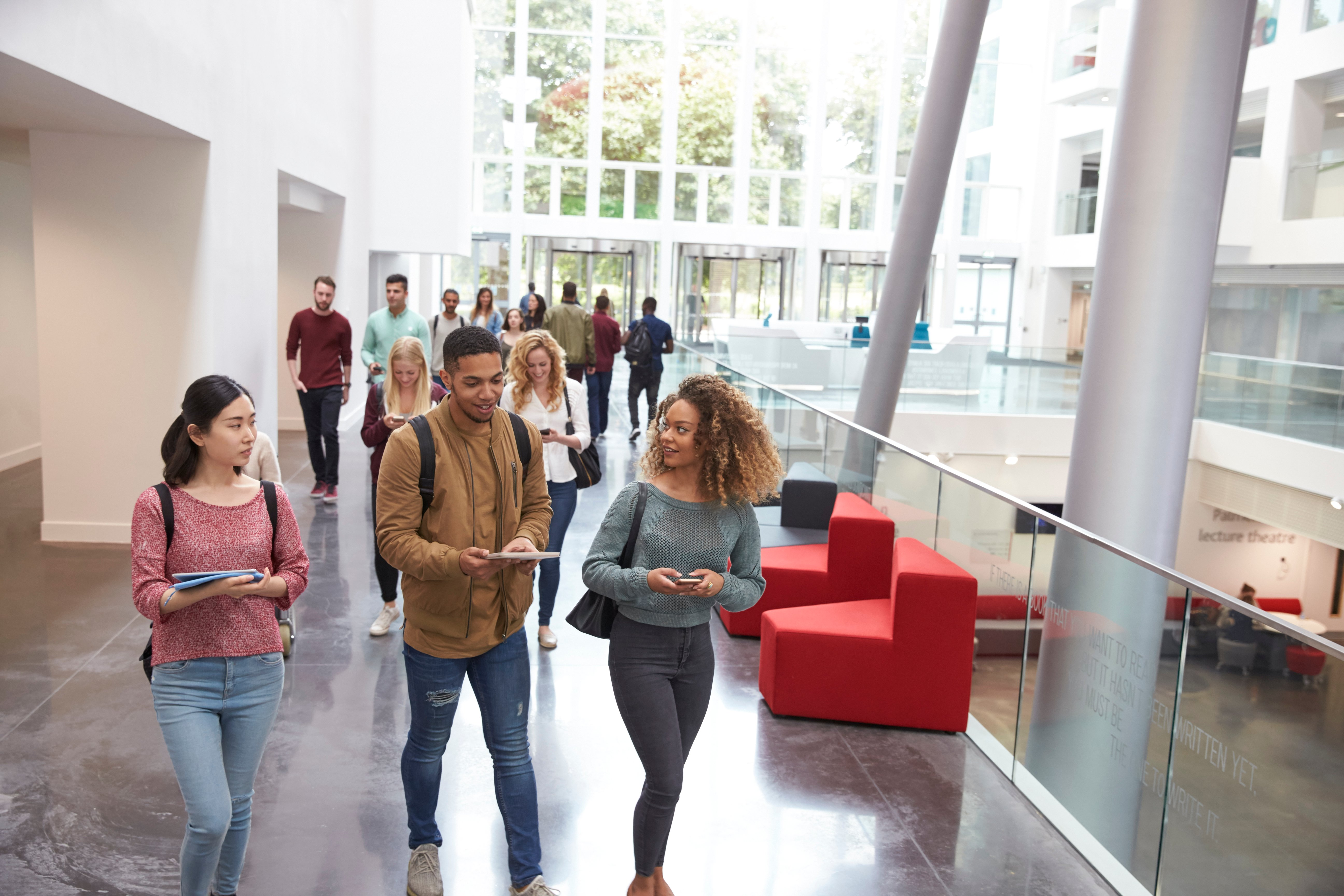 A group of students walk through a large modern university building
