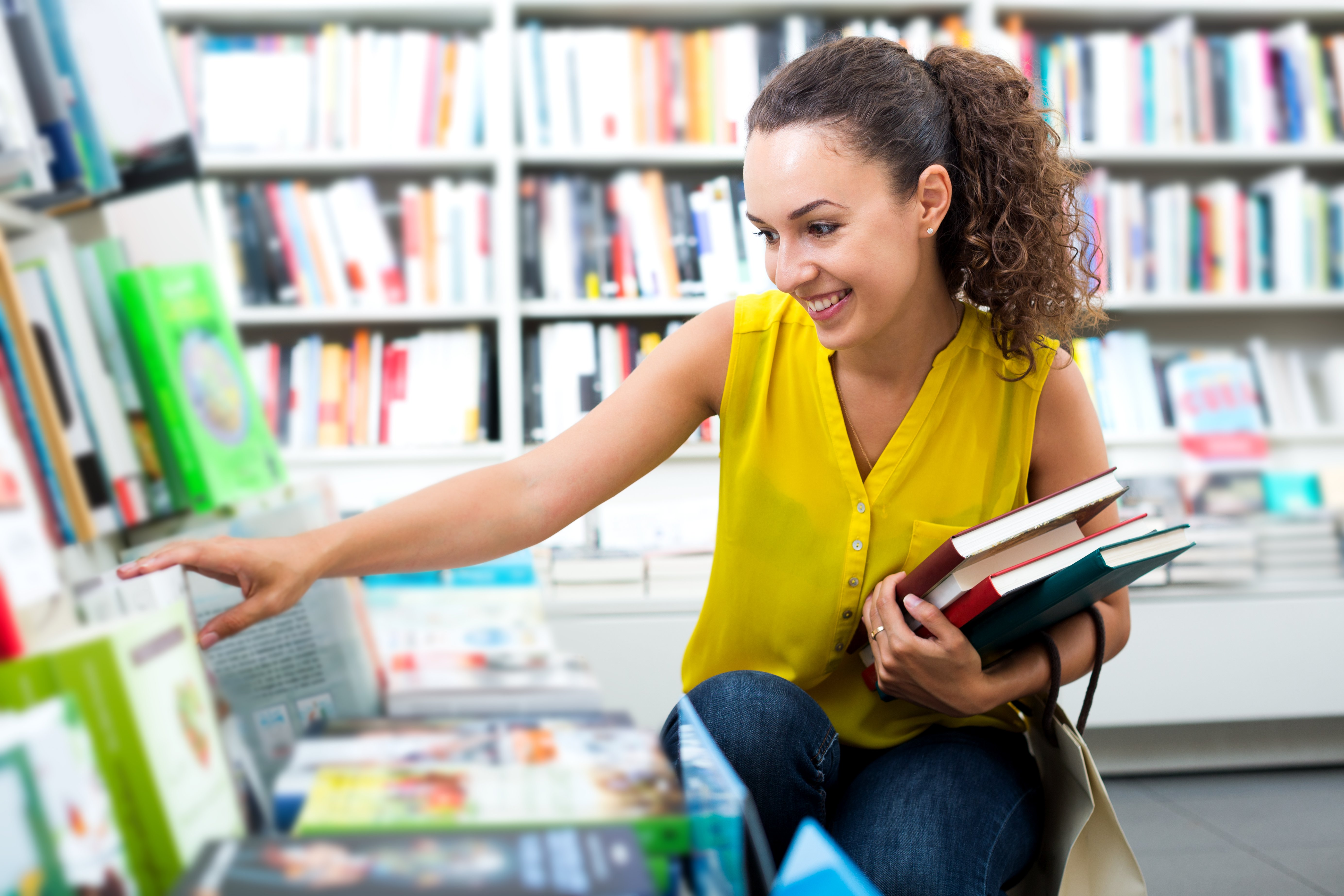 A woman in a yellow top and blue jeans holds a few books and crouches down to look at more books in a bookshop