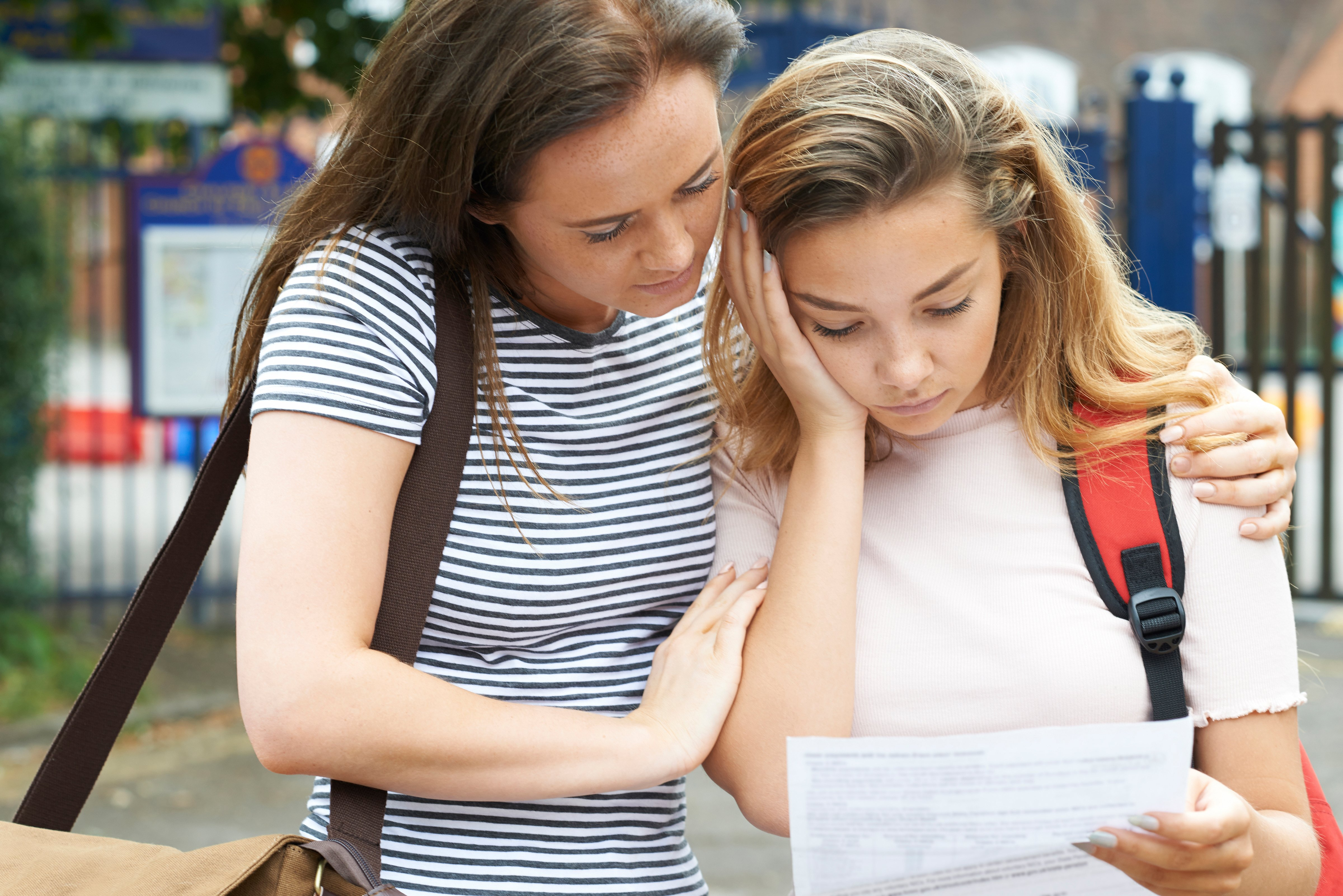A woman comforts a girl who looks upset about school results by putting her arm around her