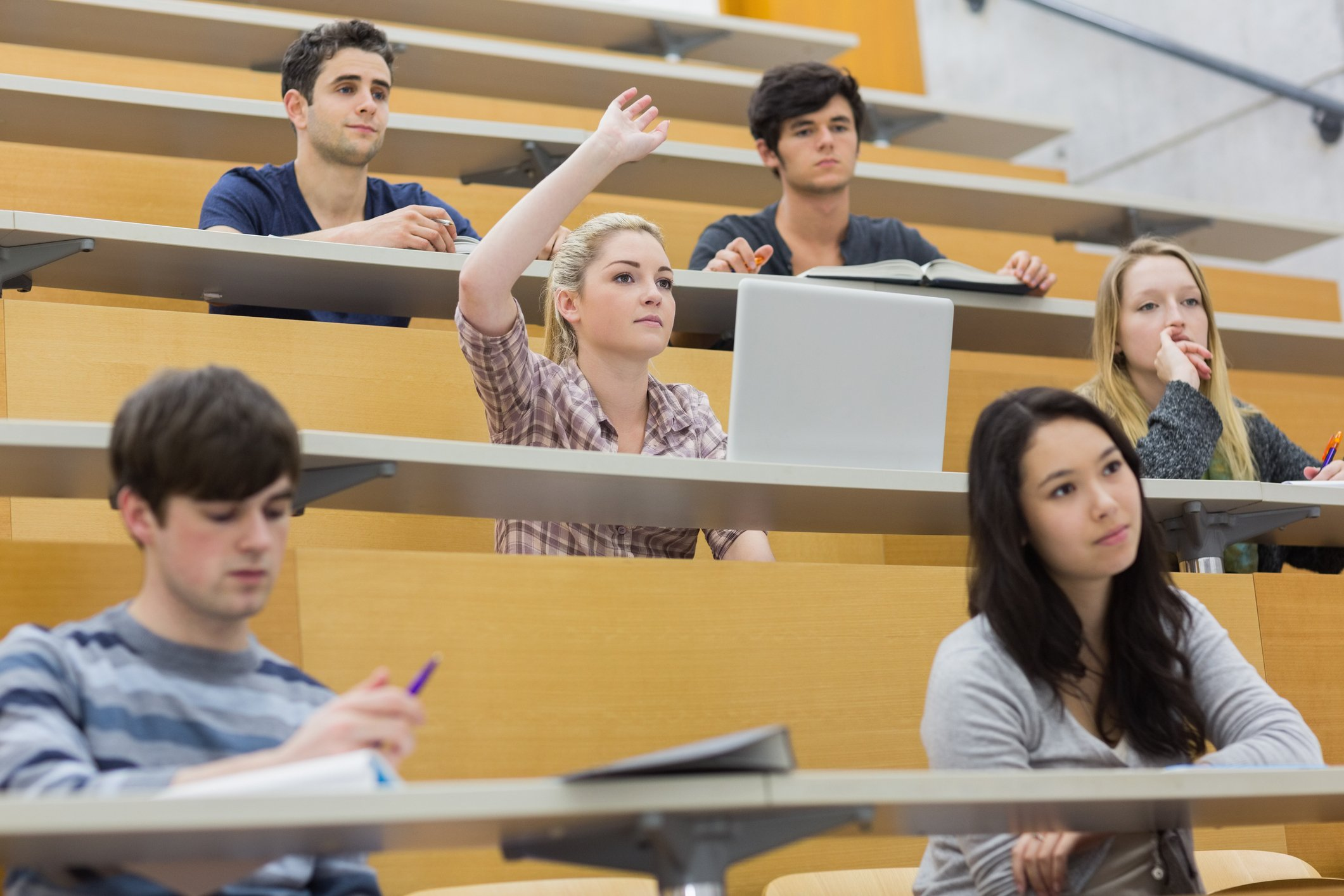 A group of students sit in a lecture theatre with a girl raising her hand to ask a question