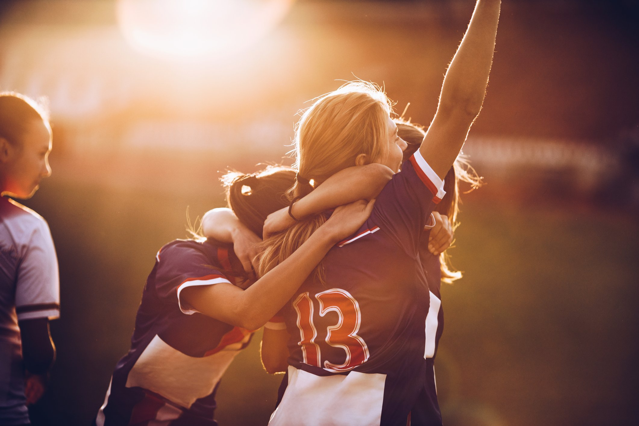 A group of girls hug each other after receiving a good sport result