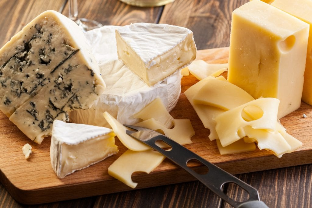 A selection of cheeses, including brie, cheddar and blue stilton, are arranged on a wooden chopping board on a wooden surface