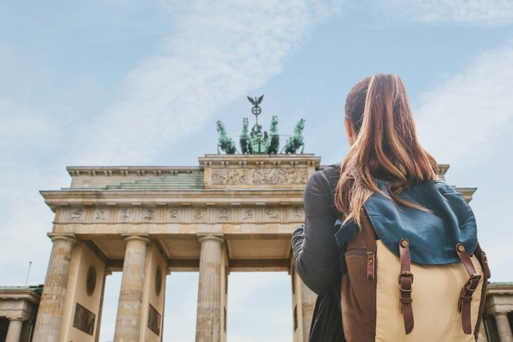 A tourist girl with a backpack on stands looking up at the Brandenberg Gate in Berlin, Germany