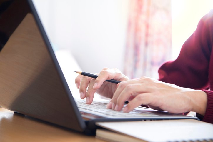 Close up of womans hands writing a legal document on a laptop