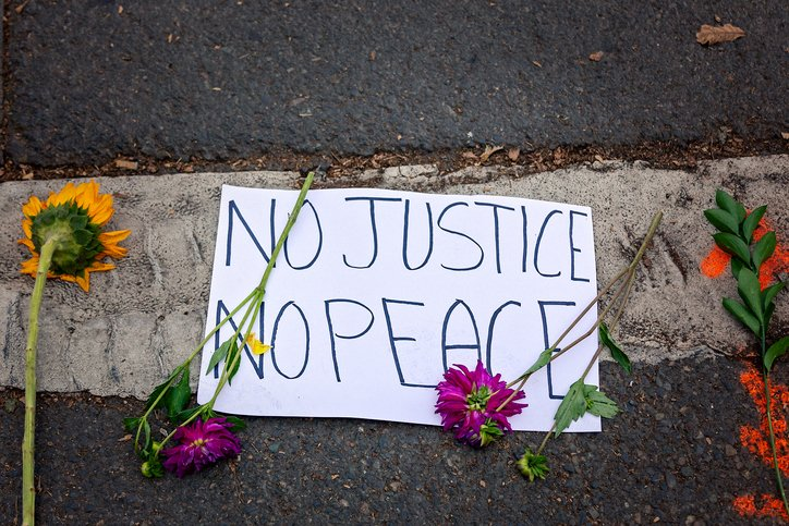 "Banner reading ""no justice, no peace"" surrounded by flowers"