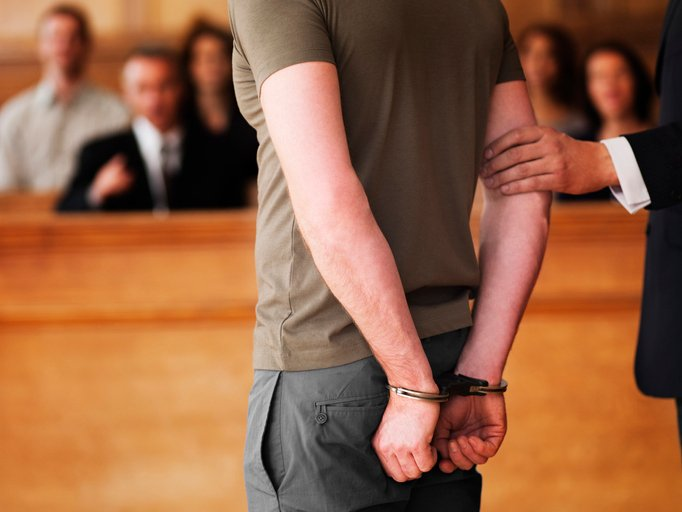 A man stands in court with his hands in handcuffs behind his back