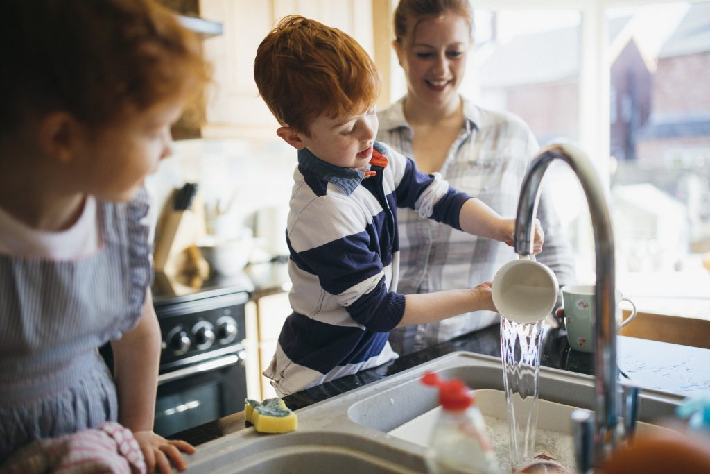 Young family washing dishes together