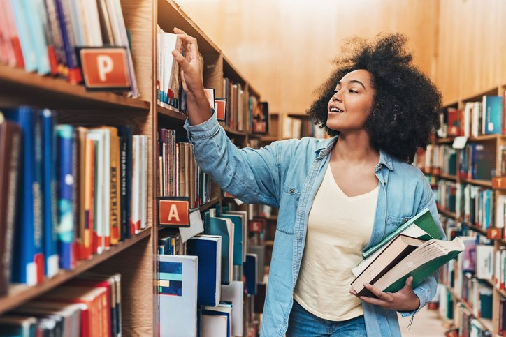 LLM student in the library choosing books