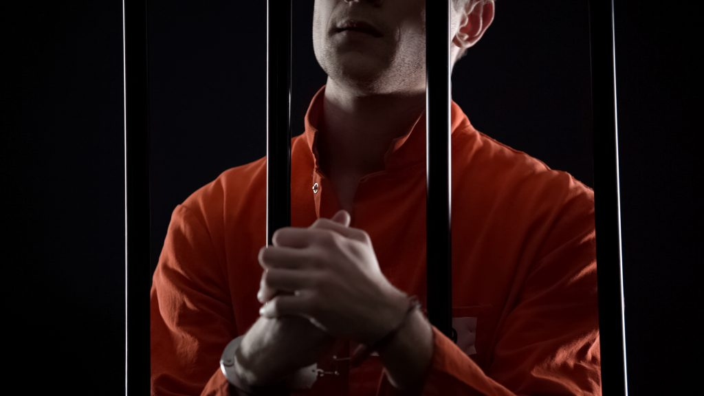 Criminal in orange jumpsuit and handcuffs behind bars