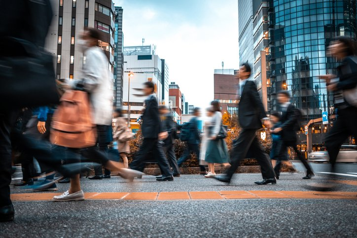 Blurred image of people walking accross a street in a metropolitan area