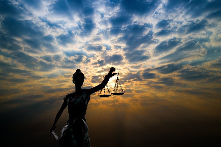 Lady justice statue against backdrop of a cloudy sunset