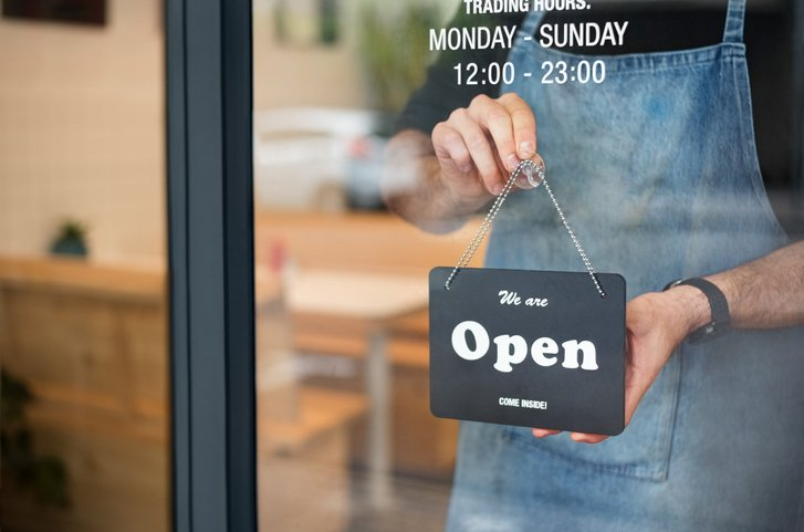 """Shop worker placing an """"open"""" sign in the shop window"""