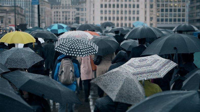 Crowd of people using umbrellas on a street during a storm
