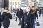 Woman wearing a facemask walking down a london street with a red bus and other pedestrians behind her
