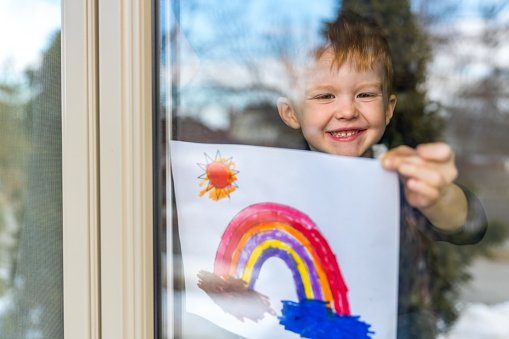 Toddler sticking a painting of a rainbow on his window during the COVID-19 pandemic
