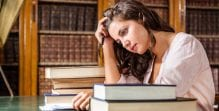 A girl sits at a table surrounded by books and looks sad about all the work she has to do