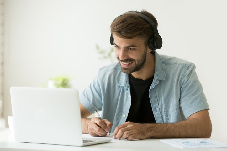 A man sits with headphones on in front of his open white laptop