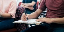 Students sit in a classroom writing on paper